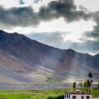 Sunlight streaming over a house set in the fields around Kaza in the Spiti Valley.