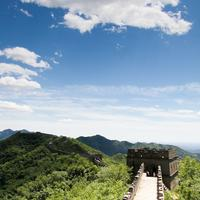 Tourists enjoying a leisurely stroll on the sunlit Mutianyu great wall.