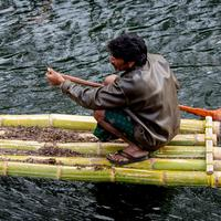 A local tribesman paddling across the Vandal river using bamboo rafts.