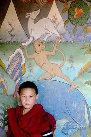 A novice monk infront of a colorful painting at the colorful Chimi Lhakhang in central Bhutan.