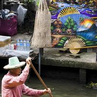 A boat passing infront of colorful stalls at the Damnoen Saduak Floating Market, Bangkok
