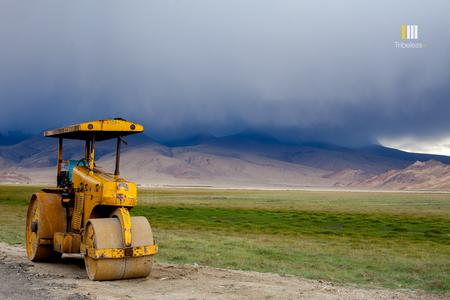 A yellow road roller parked by the roadside amid the lush fields and gathering clouds over Hanle.