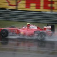 A red Ferrari F1 car zipping through the Shanghai F1 circuit.